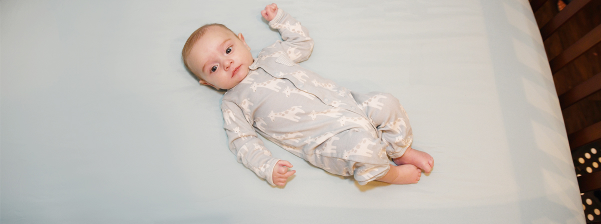 Baby lying on his back wearing a long-sleeved onesie in a crib with no pillows or blankets.