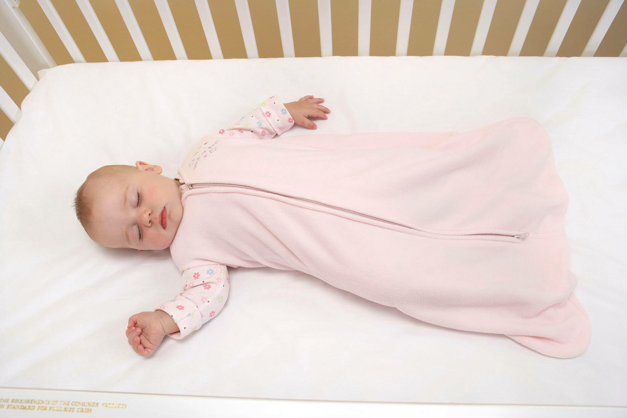 Baby in a sleep sack lying on their back on a mattress with a fitted sheet in a crib.