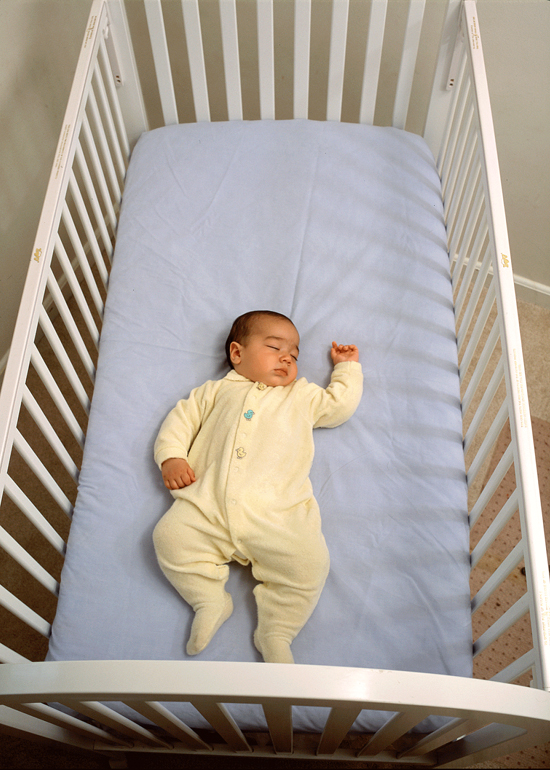 Baby lying on their back a mattress with a fitted sheet in a crib.