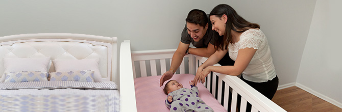 Mother and father talking to a baby laying on his back in a crib.