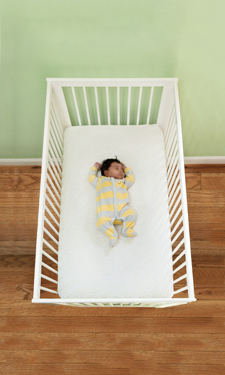 baby sleeping on its back in a safe sleep environment