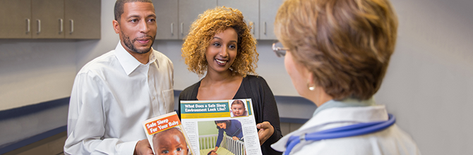 A female physician is talking to a couple holding Safe to Sleep® campaign materials.