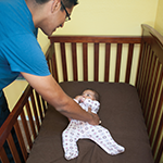 A father lays his baby down on his back in a crib, which shows a sleep safe environment free of toys, blankets, pillows, and crib bumpers.