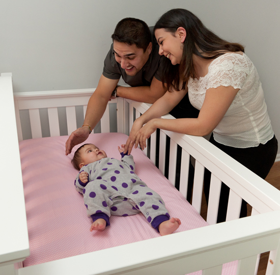 parents placing baby into a safe sleep environment