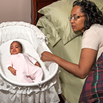 A baby sleeps on her back in a bassinet, which is next to her mother's bed. Her mother lies in her own bed and rests her hand on the side of the baby's bassinet.